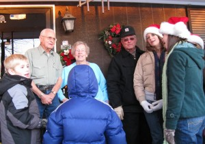 An elderly couple greet the carolers on their front porch.